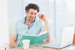Smiling casual businessman with books at his desk Royalty Free Stock Images