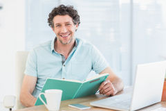 Smiling casual businessman with books at his desk Stock Photo