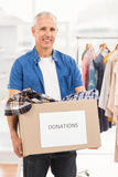 Smiling casual businessman holding donation box Stock Photography
