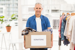 Smiling casual businessman holding donation box. Portrait of smiling casual businessman holding donation box in the office Royalty Free Stock Images