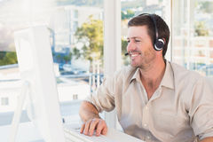 Smiling casual businessman listening to computer at desk Royalty Free Stock Photography