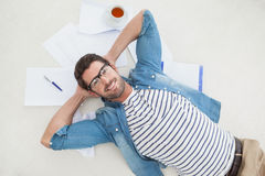 Smiling casual businessman lying on files Royalty Free Stock Image