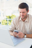 Smiling casual businessman sending a text at his desk Royalty Free Stock Images