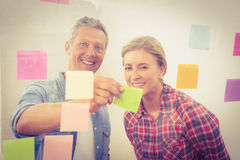 Smiling casual businessman showing sticky note to colleague Royalty Free Stock Image