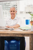 Smiling casual businessman sitting on exercise ball at desk Stock Photo