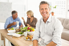 Smiling casual businessman sitting on table at lunch Stock Image