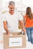 Smiling casual businessman sorting donations. In the office Stock Images