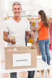 Smiling casual businessman sorting donations. Portrait of smiling casual businessman sorting donations in the office Royalty Free Stock Photography