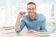 Smiling casual businessman studying at his desk Stock Photos