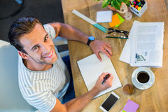 Smiling casual businessman writing in notepad Stock Image