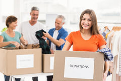 Smiling casual businesswoman holding donation box Royalty Free Stock Image