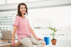 Smiling casual businesswoman leaning on desk Royalty Free Stock Image