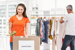 Smiling casual businesswoman sorting donations. Portrait of smiling casual businesswoman sorting donations in the office stock photos