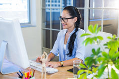 Smiling casual businesswoman working on computer Royalty Free Stock Photos