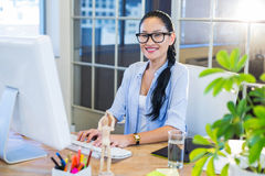 Smiling casual businesswoman working on computer Royalty Free Stock Photography