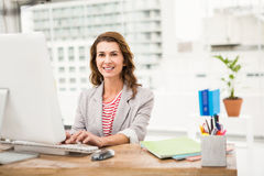 Smiling casual businesswoman working with computer Stock Photography