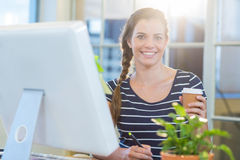 Smiling casual businesswoman working on digitizer and holding coffee Stock Photography