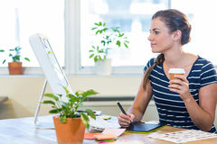 Smiling casual businesswoman working on digitizer and holding coffee Stock Photos