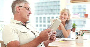 Smiling casual colleagues using digital tablet in office stock video