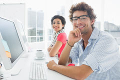 Smiling casual couple at desk in office Royalty Free Stock Photography
