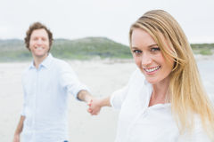Smiling casual couple holding hands at beach Royalty Free Stock Photos