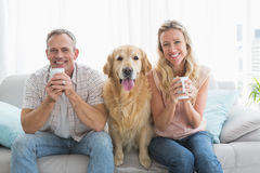 Smiling casual couple sitting on couch having coffee Royalty Free Stock Photo