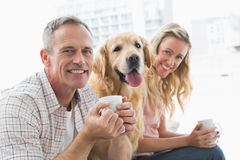 Smiling casual couple sitting on couch having coffee Stock Photography