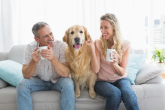 Smiling casual couple sitting on couch having coffee Royalty Free Stock Images