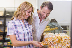 Smiling casual couple taking a pastry Royalty Free Stock Images
