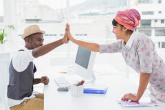 Smiling casual coworkers high fiving Royalty Free Stock Image