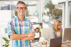 Smiling casual designer in front of his working colleague. Portrait of smiling casual designer in front of his working colleague in the office Royalty Free Stock Images