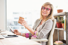 Smiling casual designer using smartphone Royalty Free Stock Images