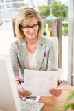 Smiling casual designer working at her desk Stock Photos