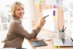 Smiling casual designer working at her desk Stock Photography