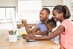 Smiling casual family on a computer Stock Image