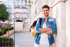 Smiling casual man with backpack and arms folded Royalty Free Stock Image