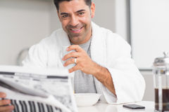 Smiling casual man with coffee cup reading newspaper in kitchen Stock Photography