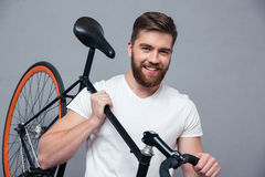 Smiling casual man holding bicycle on the shouder. Portrait of a smiling casual man holding bicycle on the shouder over gray background Stock Photography