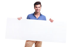 Smiling casual man holding big blank board Stock Photos