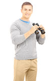 Smiling casual man holding a binocular and looking at camera Royalty Free Stock Images