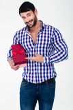 Smiling casual man holding gift box. Portrait of a smiling casual man holding gift box isolated on a white background Royalty Free Stock Photos