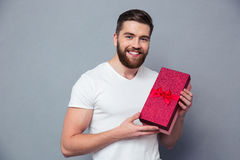 Smiling casual man holding gift box. Portrait of a smiling casual man holding gift box over gray background and looking at camera Royalty Free Stock Photography