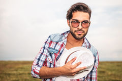 Smiling casual man holding his hat against chest Stock Photos