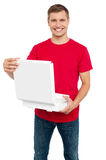 Smiling casual man holding pizza box Stock Photo