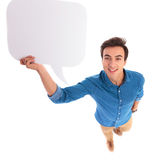 Smiling casual man holding a speech bubble above his head Royalty Free Stock Images