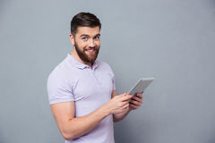 Smiling casual man holding tablet computer. Portrait of a smiling casual man holding tablet computer and looking at camera over gray background Royalty Free Stock Image