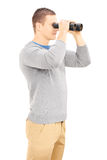 Smiling casual man looking through binocular Stock Photo