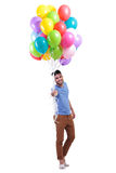 Smiling casual man is offering a bunch of balloons