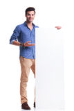 Smiling casual man presenting a big empty board. On white background Stock Images