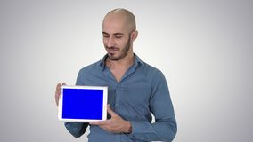 Smiling casual man presenting a tablet with a blank screen on gradient background. stock video footage